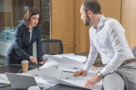 architects discussing building plans together at modern office