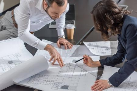 Photo for High angle view of architects working with building plans together at office - Royalty Free Image
