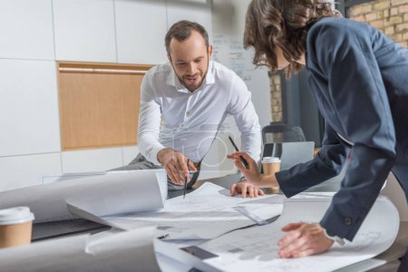 Photo for Architects working with building plans together at modern office - Royalty Free Image