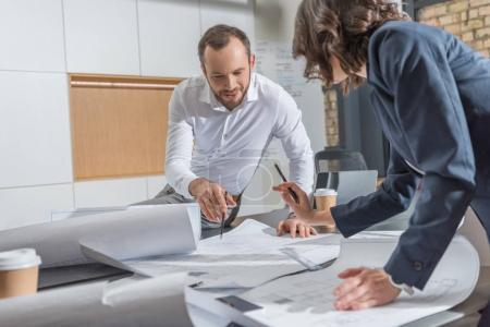 Photo pour Architectes travaillant avec des plans de construction ensemble au bureau moderne - image libre de droit