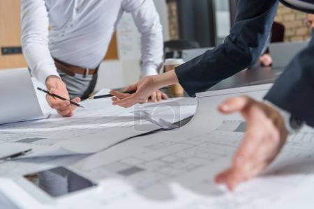 Photo pour Recadrée tir des architectes de remue-méninges sur des plans de construction - image libre de droit