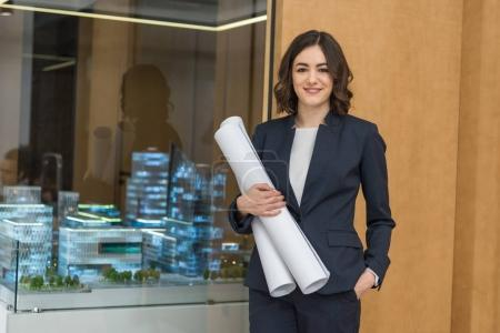 beautiful young architect with rolled building plans