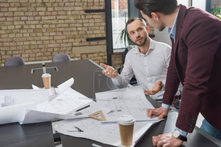 Photo for Successful architects brainstorming over building plans at office - Royalty Free Image