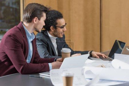 Photo pour Heureux jeunes architectes travaillent ensemble avec ordinateur portable au bureau - image libre de droit
