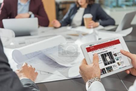 cropped shot of architect using tablet with bbc website on screen while having conference