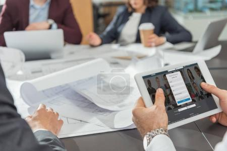 Photo for Cropped shot of architect using tablet with linkedin website on screen while having conference - Royalty Free Image
