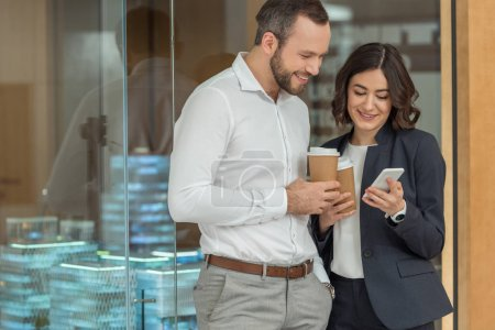 colleagues drinking coffee and using smartphone together