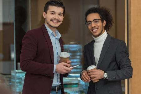 happy young businessmen with paper cups of coffee at office