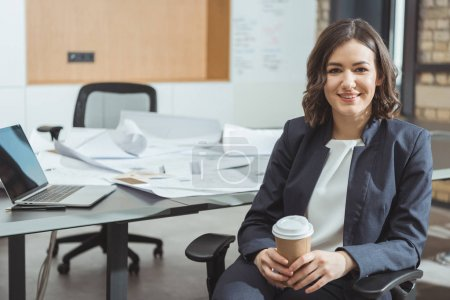 beautiful young architect with coffee to go in front of workplace