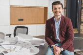 smiling young architect sitting on work table with building plans at office
