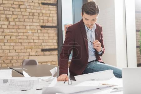 thoughtful young architect sitting on work table with building plans at office