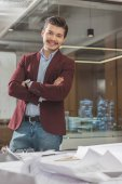 handsome young architect with crossed arms near workplace at office
