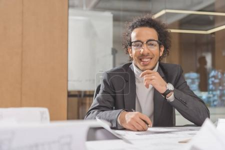 smiling young architect with building plans sitting at workplace at office