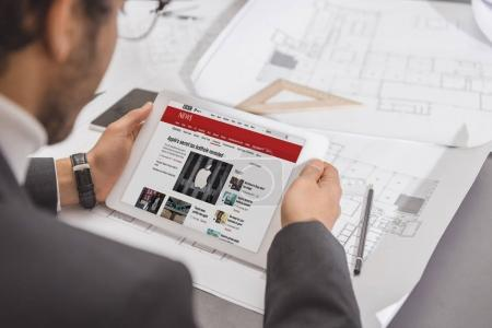 cropped shot of young architect using tablet at workplace with bbc website on screen
