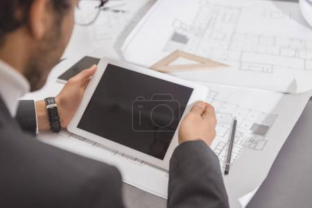 cropped shot of young architect using tablet at workplace