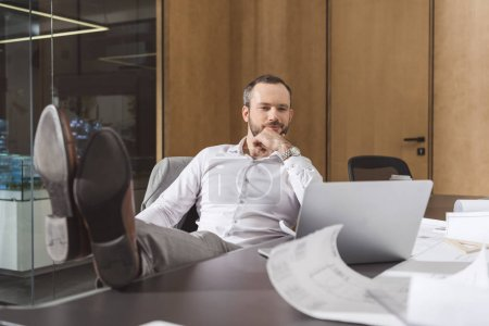 handsome thoughtful architect sitting at workplace and looking at laptop