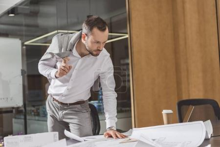 handsome architect looking at building plans on desk at office