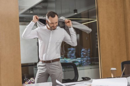 handsome architect putting on suit and looking at plans at office