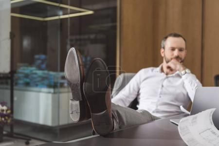 handsome successful architect relaxing at workplace at office