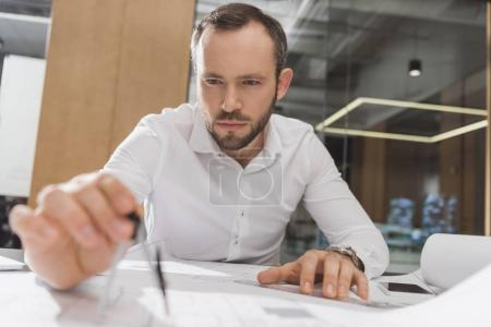 handsome architect with compass drawing building plans at office