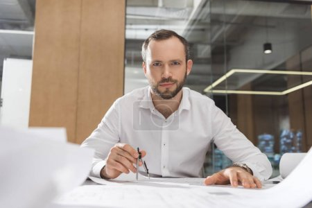 handsome successful architect with compass working on building plans at office