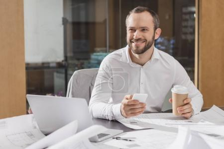 happy architect with paper cup of coffee using smartphone at office