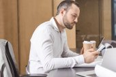 serious architect with paper cup of coffee using smartphone at office
