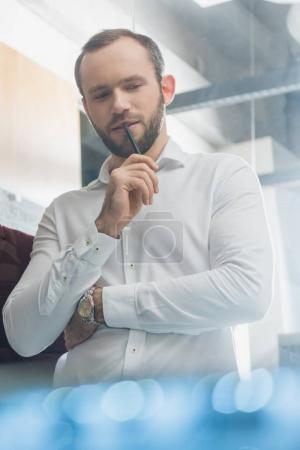 Photo for Bottom view of thoughtful architect in white shirt at office - Royalty Free Image