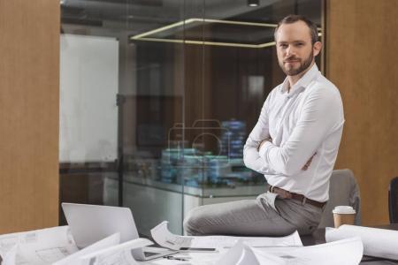 Photo pour Architecte réussi assis sur la table avec les bras croisés au bureau et regardant la caméra - image libre de droit