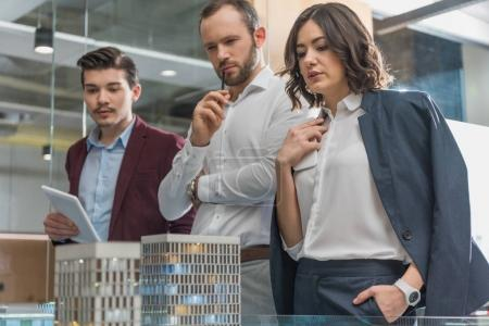 team of thoughtful architects looking at miniature town model