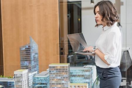 beautiful young architect using laptop near building models