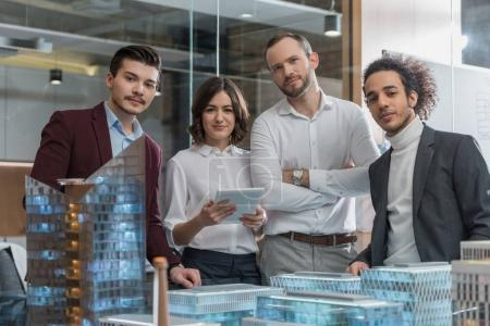 group of successful architects standing next to building models at office