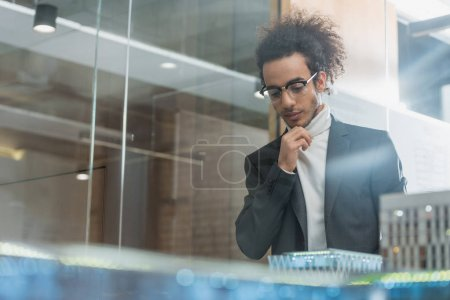 thoughtful young architect in suit near buildings miniature model at office