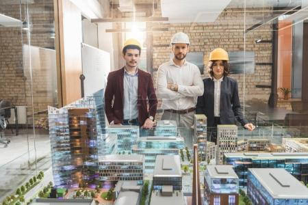 team of architects in hard hats in front of miniature town model at office
