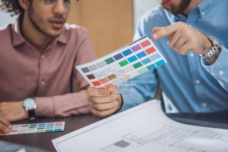 cropped shot of designers choosing colors from palette for project