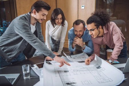 group of professional architects discussing building plans at office
