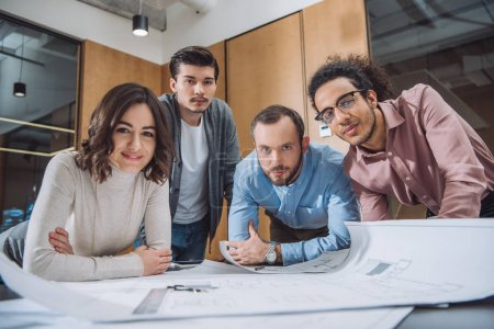 group of successful architects working on plans together at office