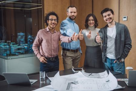 group of successful architects showing thumbs up at office