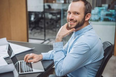 happy successful architect working with laptop at office