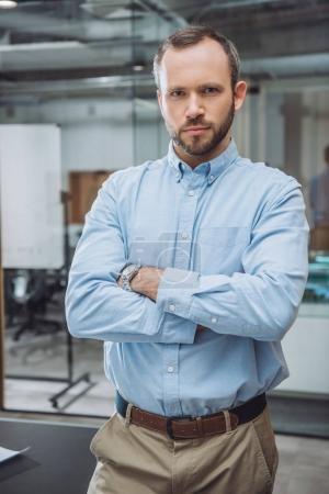 Photo pour Bel homme d'affaires prospère avec les bras croisés au bureau - image libre de droit