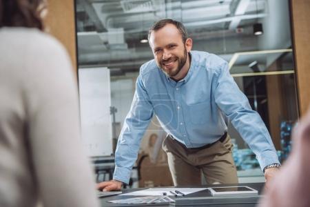 Photo pour Homme d'affaires adulte heureux parlant à des collègues au bureau - image libre de droit