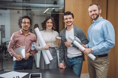 Photo for Group of successful architects with rolled plans at office - Royalty Free Image
