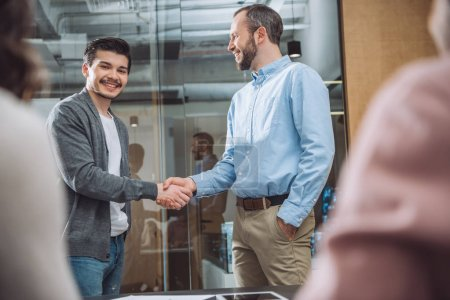 smiling business colleagues shaking hands at modern office