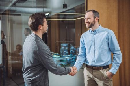 happy business colleagues shaking hands at office