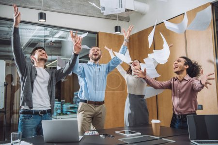group of successful businesspeople throwing up documents at office