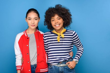 smiling african american and asian friends posing isolated on blue