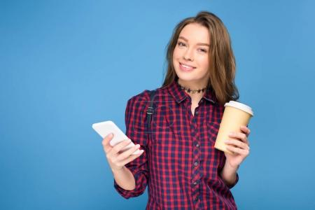 Photo for Beautiful smiling girl with coffee using smartphone, isolated on blue - Royalty Free Image