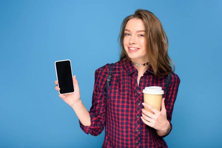 beautiful young girl holding cup on coffee and showing smartphone, isolated on blue