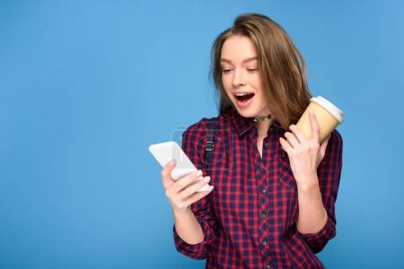 surprised girl with coffee to go using smartphone, isolated on blue