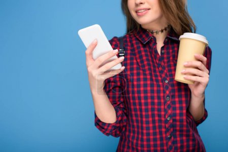 Photo for Cropped view of young girl with coffee to go using smartphone, isolated on blue - Royalty Free Image